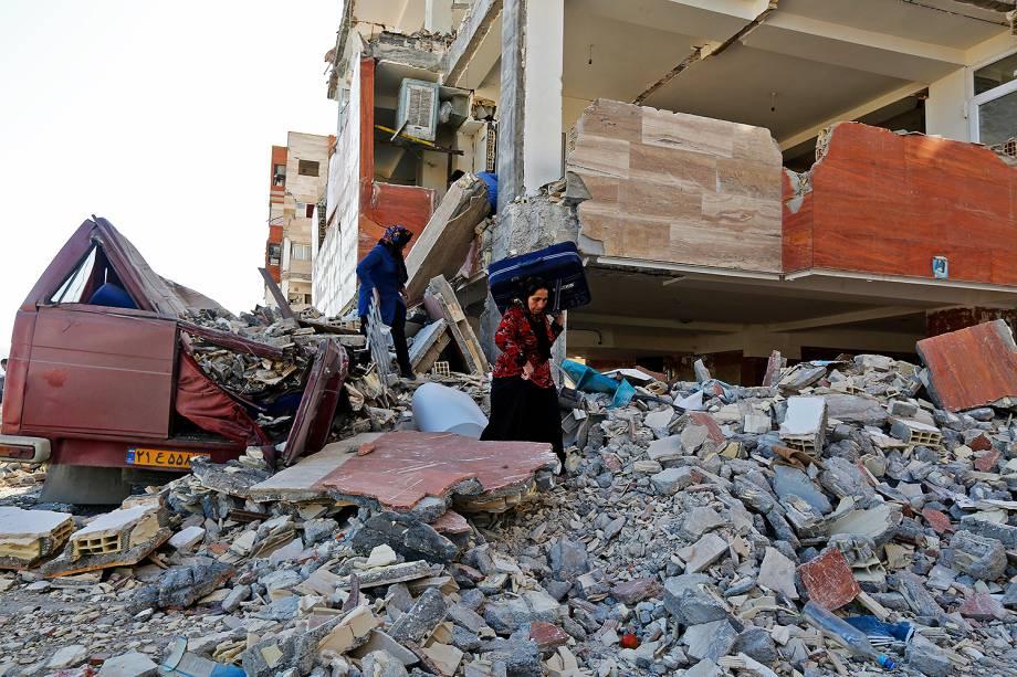 Sobrevivente do tremor carrega pertences para fora de prédios danificados em Sarpol-e Zahab, após terremoto atingir a fronteira entre o Iraque e o Irã - 14/11/2017
