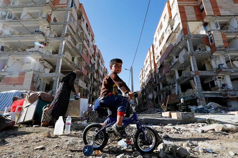 Garoto brinca ao lado de prédios danificados em Sarpol-e Zahab, após terremoto atingir a fronteira entre o Iraque e o Irã - 14/11/2017