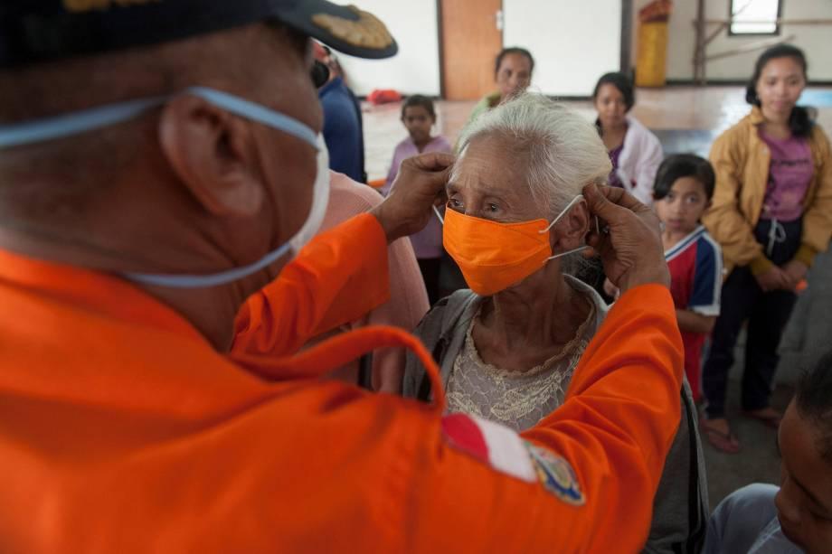 Oficial da agência de gerenciamento de desastres BPBD coloca uma máscara em uma mulher idosa em um abrigo para residentes que tiveram que deixar suas casas devido à erupção do vulcão Monte Agung em Bali, na Indonésia - 27/11/2017