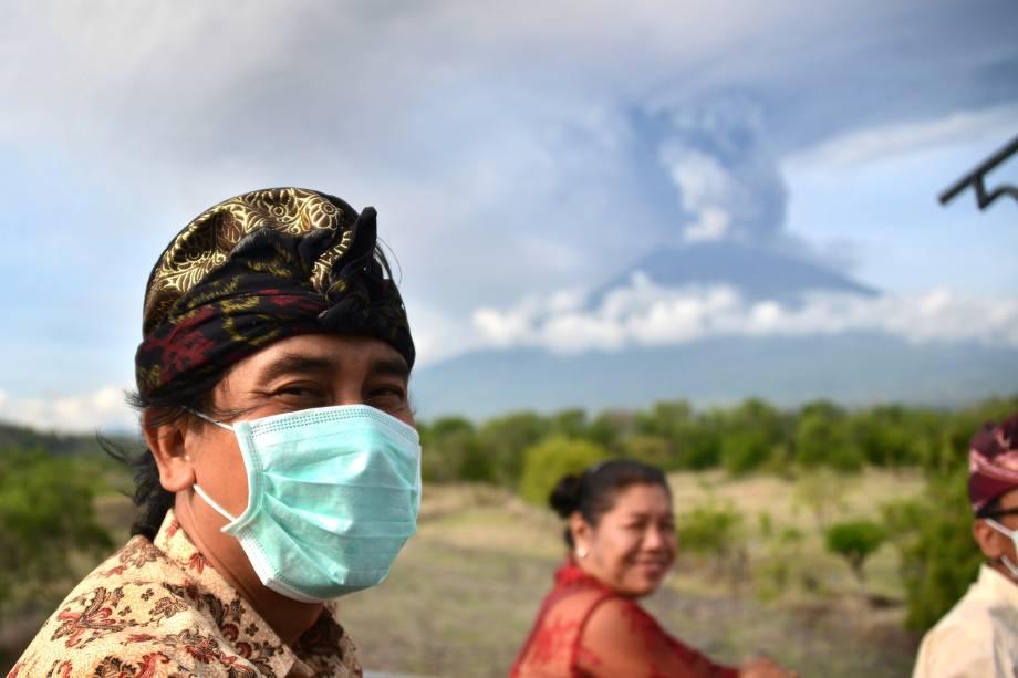 Balineses passam em frente ao Monte Agung durante uma erupção vista do subdistrito de Kubu em Karangasem Regency, na ilha turística de Bali, na Indoésia - 27/11/2017