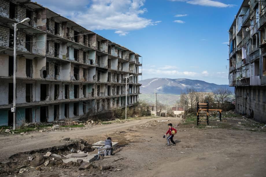 Crianças brincam próximo a um prédio destruído pela guerra, em Artsakh.