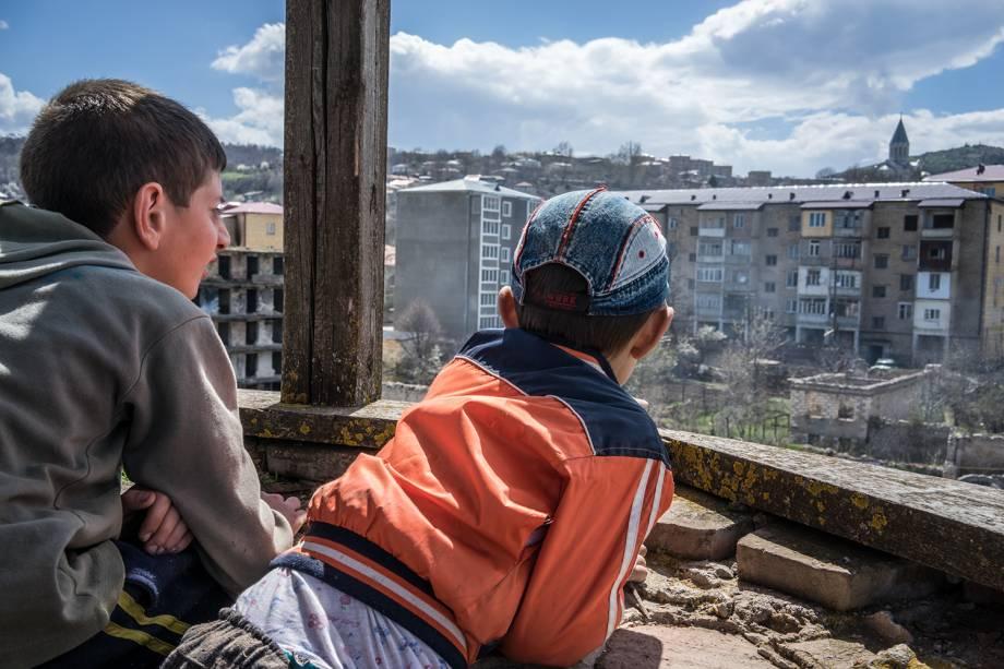 Crianças observam prédios destruídos pela guerra em Artsakh.