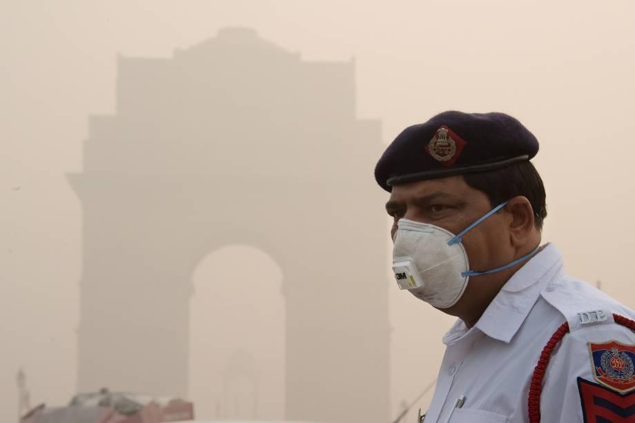 Policial indiano usa uma máscara de proteção enquanto trabalha perto do portão da Índia, em meio a poluição pesada em Nova Deli - 09/11/2017