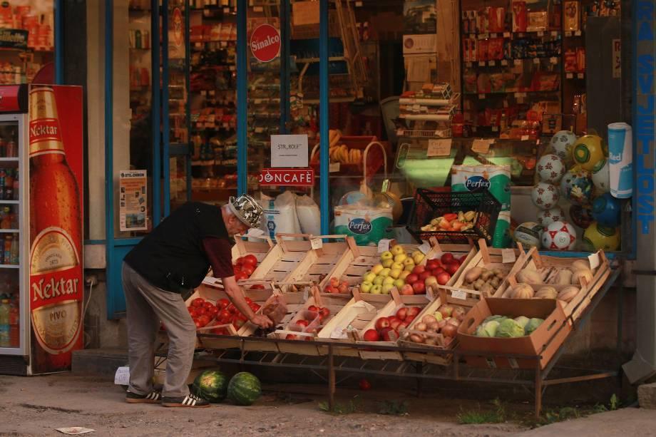 Um homem organiza os alimentos na vitrine de uma mercearia na região da República Srpska, no leste da Bósnia.
