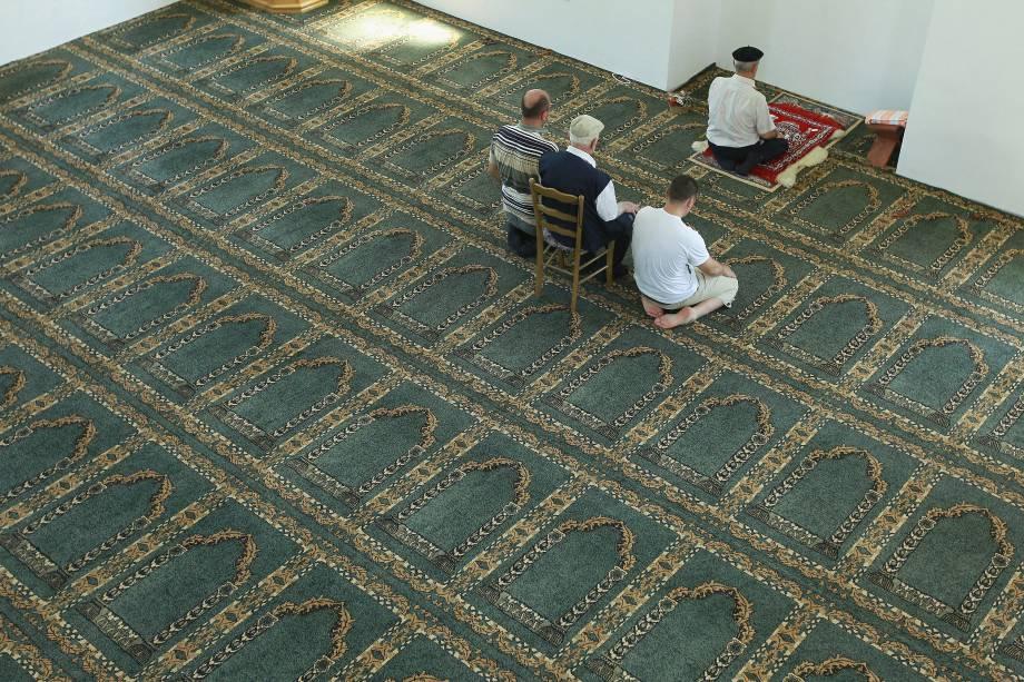 Quatro homens muçulmanos rezam em uma mesquita reconstruída com financiamento do Irã na região da Republika Srpska.