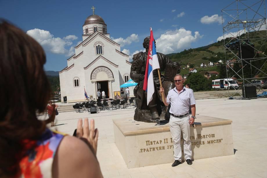 Homem segura bandeira sérvia, na aldeia de Andricgrad, República Srpska.