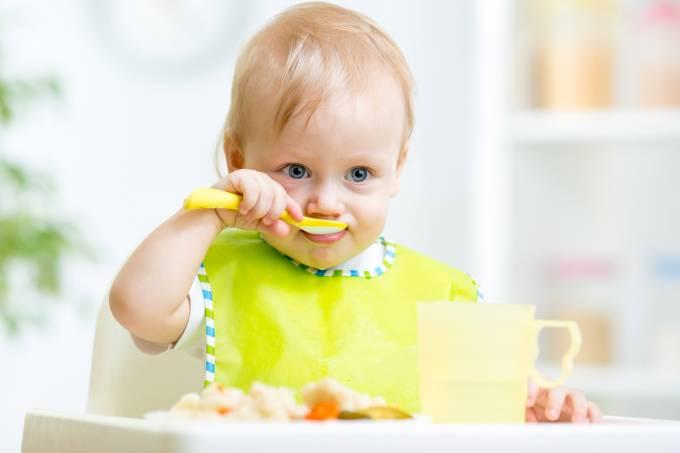 Criança comendo com colher