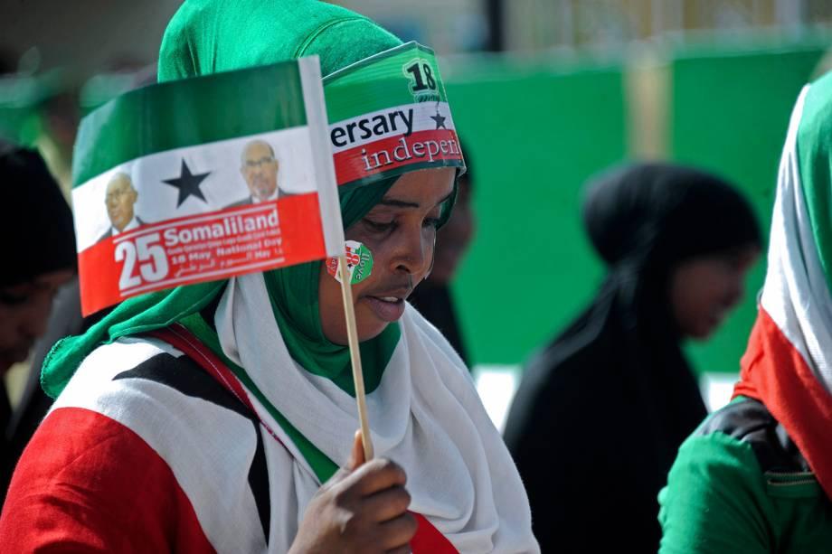 Mulher balança bandeira durante desfile do Dia da Independência em Hargeisa, Somalilândia.
