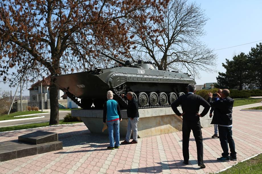 Pessoas tiram foto em frente a um blindado soviético em Tiraspol, na Transnístria.