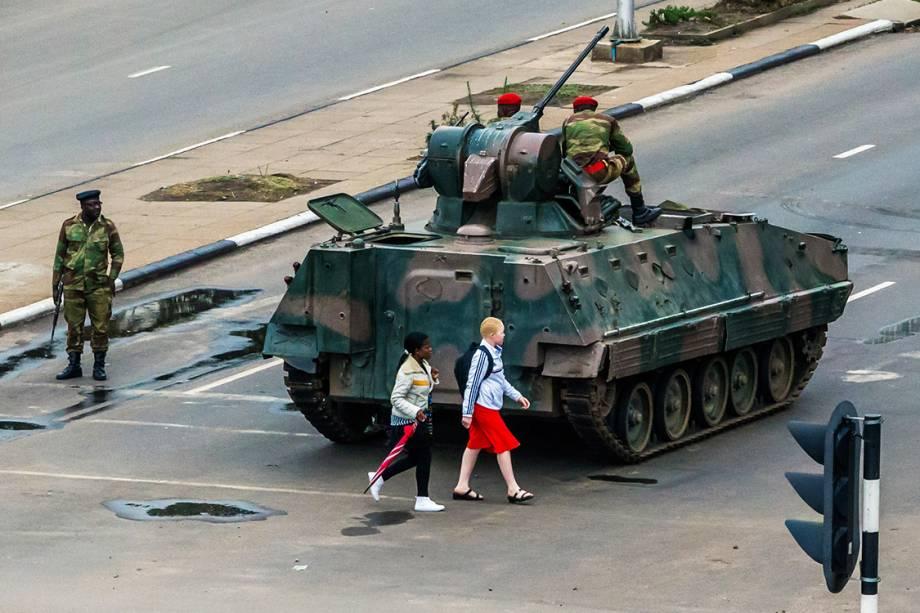 Mulheres caminham próximo a um tanque de guerra, na cidade de Harare, Zimbábue - 15/11/2017