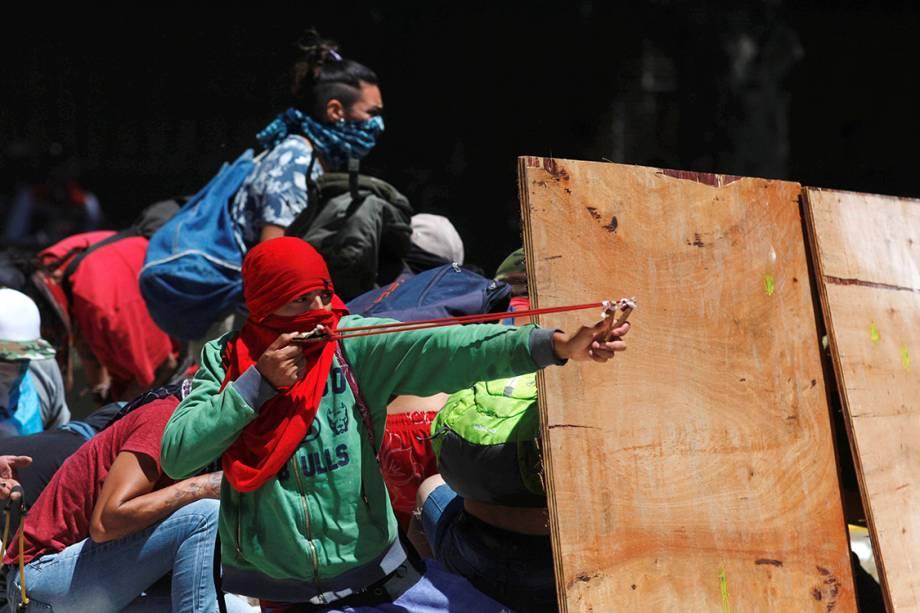 Manifestantes atiram pedras com estilingues durante protesto contra as reformas da previdência social em Buenos Aires, na Argentina