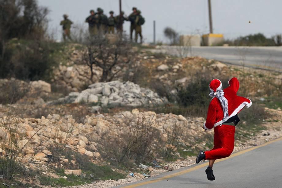 Manifestante vestido de Papai Noel atira pedras em direção à tropas israelenses durante protesto contra a decisão de Donald Trump de mover a embaixada americana em Israel de Tel-Aviv para Jerusalém - 19/12/2017