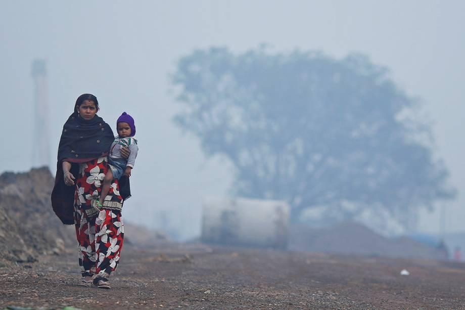 Mulher carrega filho do colo e caminha por uma estrada em Nova Délhi, na Índia - 20/12/2017