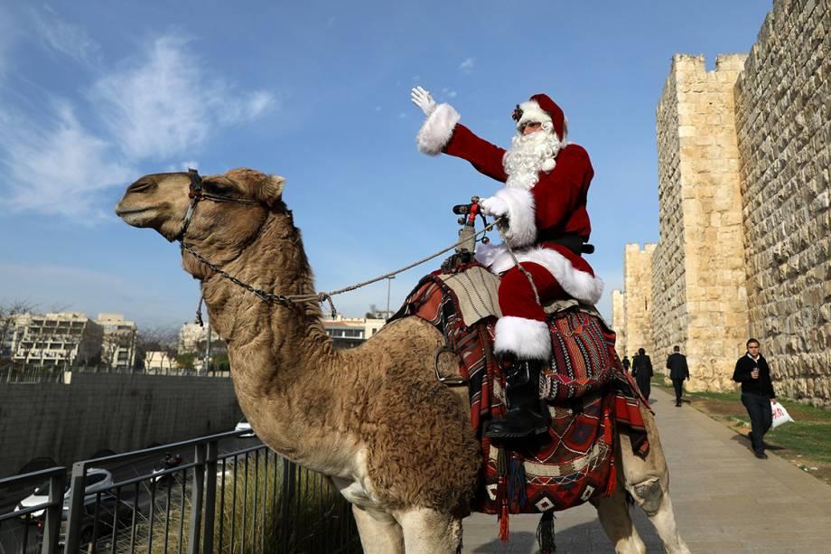 Papai Noel fantasiado cumprimenta crianças enquanto monta em um camelo, no centro de ditribuições de árvores de natal na cidade velha de Jerusalém - 21/12/2017