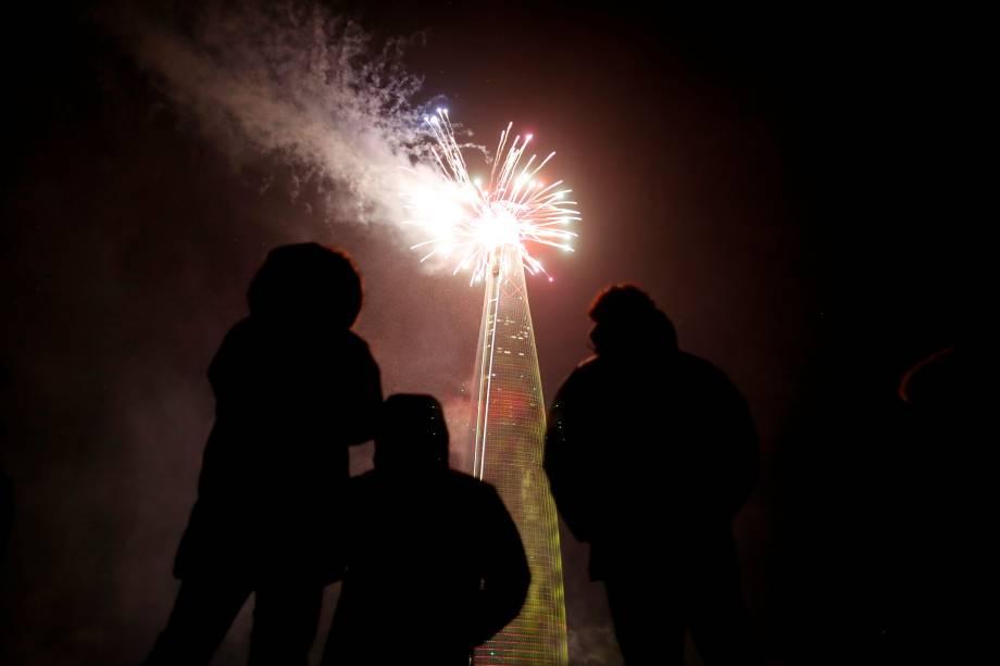 Pessoas acompanham a queima de fogos sobre o arranha-céu de 123 andares Lotte World Tower durante a celebração do Ano Novo em Seul, Coreia do Sul