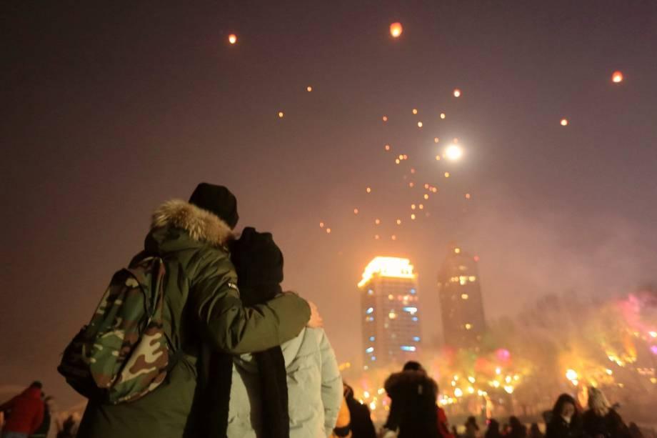 Pessoas observam enquanto lanternas são lançadas ao céu durante as celebrações do Ano Novo no rio Songhua em Harbin, na província de Heilongjiang, na China
