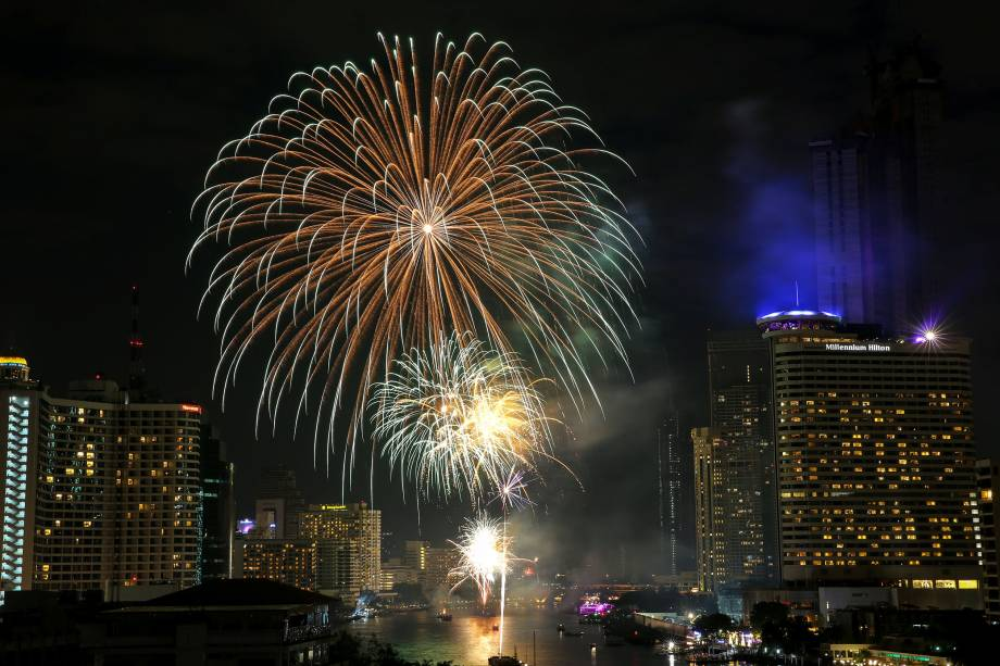 Fogos de artifício explodem sobre o rio Chao Phraya, em Bangcoc, capital da Tailândia, durante a celebração do Ano Novo