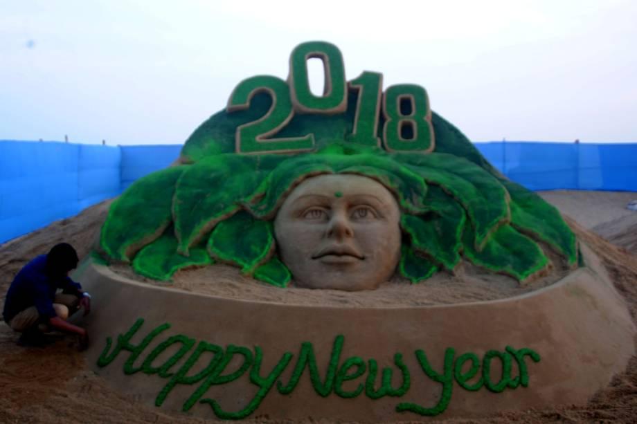 Artista de areia faz escultura para visitantes na costa leste de praia no Golfo de Bengala, na Índia, celebrando o Ano Novo
