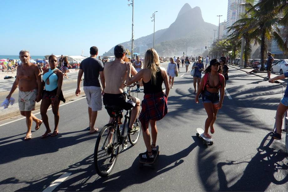 Pessoas caminham no calçadão da praia do Leblon, no Rio de Janeiro