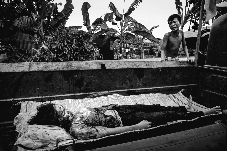 Menino vietnamita chora ao ver o corpo da irmã