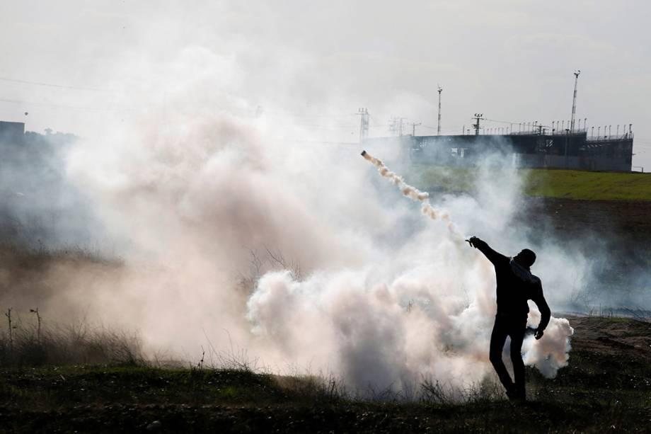 """Manifestante palestino atira de volta uma bomba de gás lacrimogênio contra as tropas israelenses, durante protesto intitulado  """"dia de raiva"""", em resposta à atitute do presidente Donald Trump de reconhecer Jerusalém como capital de Israel - 08/12/2017"""