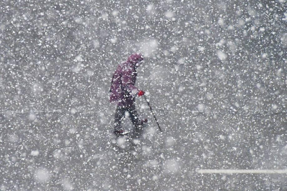 Uma pessoa é fotografada enquanto anda durante uma nevasca em Yantai, na província oriental de Shandong, China - 04/12/2017