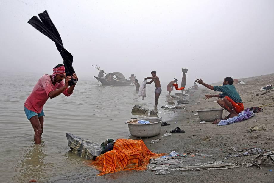 Pessoas são vistas lavando roupas nas margens do Rio Brahmaputra, durante uma manhã de inverno em Guwahati, na Índia - 04/12/2017