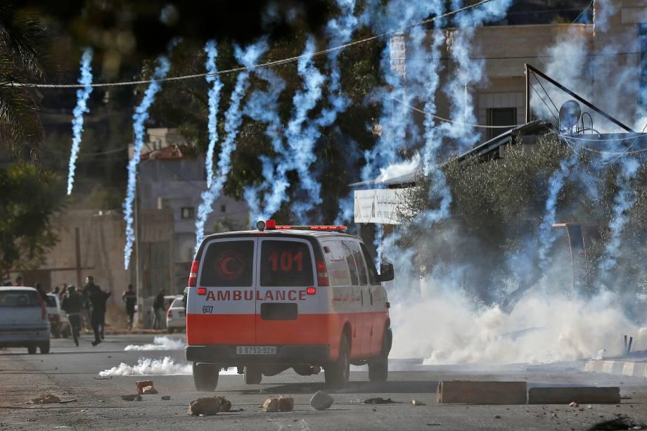 Uma ambulância palestina é vista dirigindo em meio a latas de gás lacrimogênio disparadas por soldados israelenses durante um confronto na aldeia do norte de Qusra, na Cisjordânia ocupada, perto de Nablus - 04/12/2017