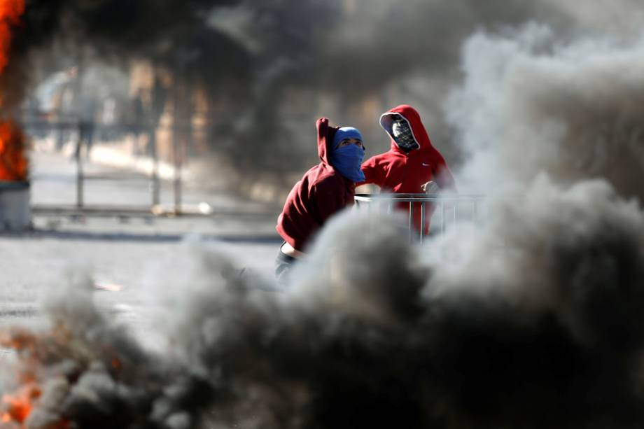 Manifestantes palestinos são vistos em meio a uma nuvem de fumaça durante confrontos com tropas israelenses na aldeia de Qusrah, na Cisjordânia - 04/12/2017
