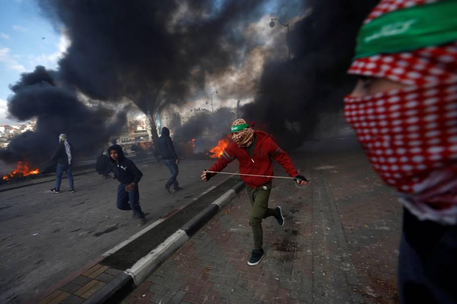 Manifestantes palestinos correm durante confrontos com tropas israelenses em um protesto contra a decisão do presidente dos Estados Unidos, Donald Trump, de reconhecer Jerusalém como a capital de Israel, perto do assentamento judeu de Beit El, nos arredores da cidade de Ramallah, na Cisjordânia - 07/12/2017