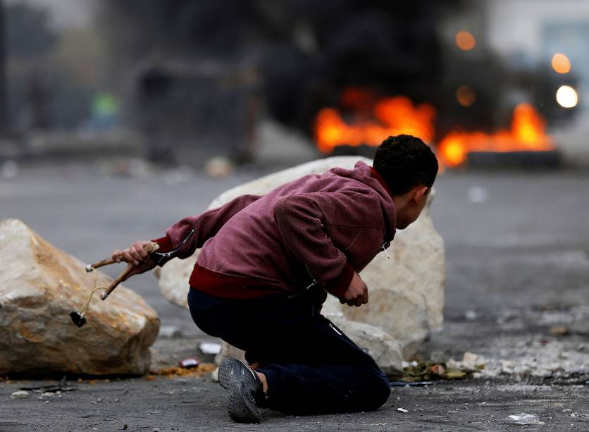 Militante palestino durante o confronto com tropas israelenses na fronteira com a cidade de Gaza - 22/12/2017