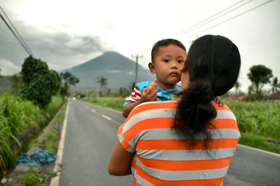 Mulher carrega seu bebê em estrada com vista para o vulcão Agung, em Bali, na Indonésia