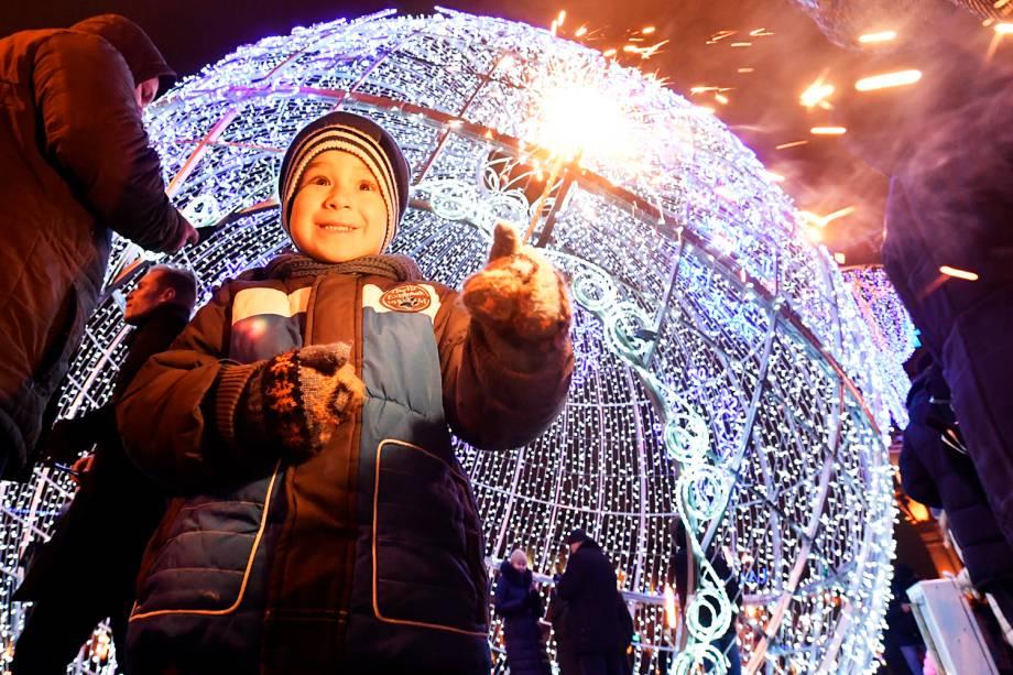 Garoto aguarda chegada do Ano Novo na região central de Minsk, capital da Bielorrússia