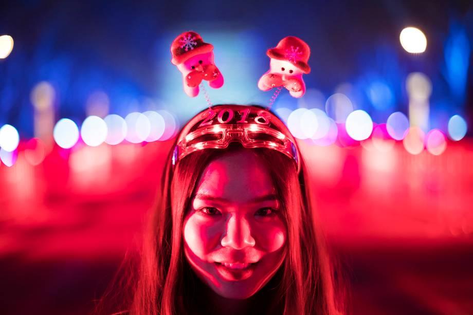 Garota posa para foto antes da tradicional contagem regressiva para a chegada do Ano Novo em Pequim, na China
