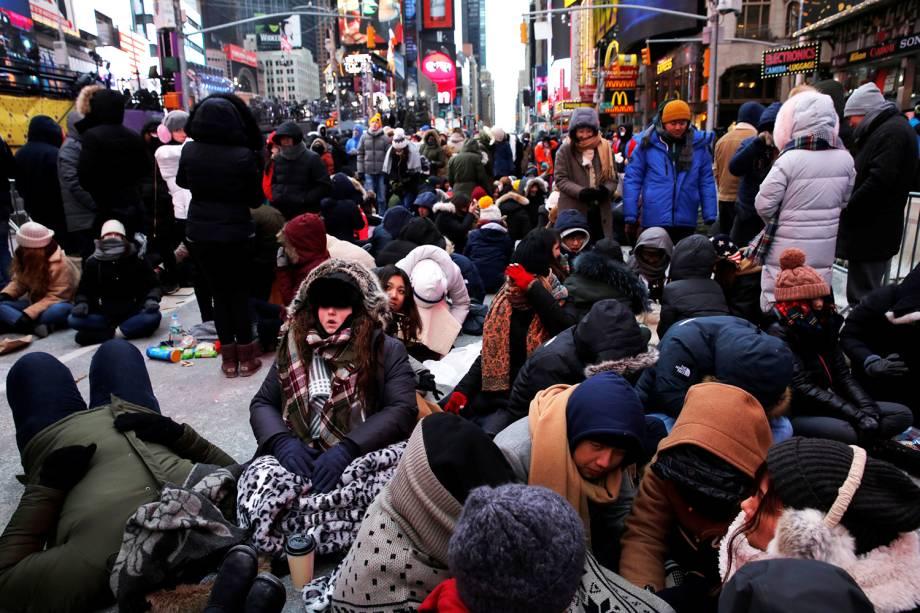 Pedestres se protegem do frio enquanto aguardam a chegada do Ano Novo na Times Square, nos Estados Unidos