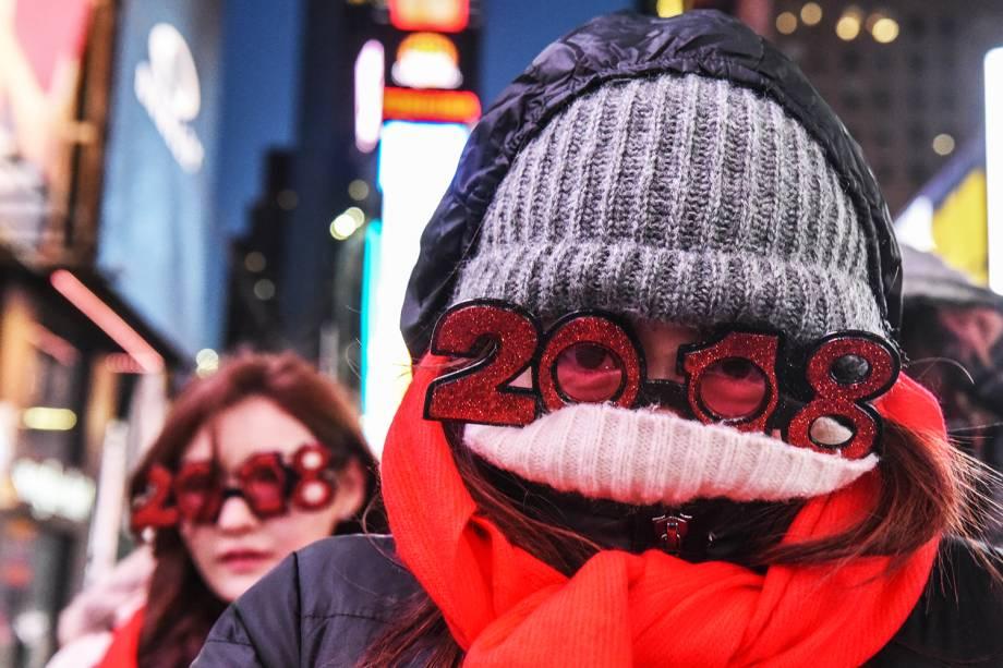 Pedestres se protegem das baixas temperaturas enquanto aguardam a chegada do Ano Novo na Times Square, nos Estados Unidos