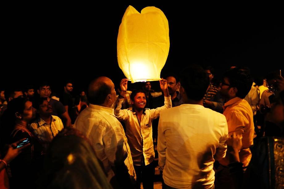 Homem segura lanterna para celebrar o Ano Novo em uma praia de Mumbai, na Índia