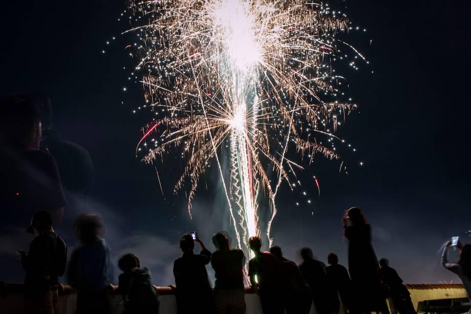 Pessoas assistem à queima de fogos na cidade de Jogjacarta, localizada na Indonésia, durante a celebração do Ano Novo