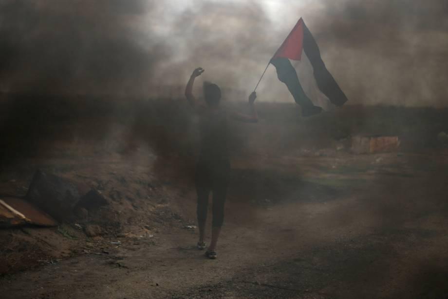 Manifestante segura uma bandeira palestina durante confronto com tropas israelenses em um protesto contra a decisão dos Estados Unidos de reconhecer Jerusalém como a capital de Israel