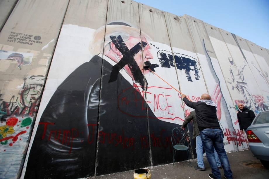 Palestino pixa um mural com a imagem do presidente dos Estados Unidos, Donald Trump, em uma parte da barreira israelense, na cidade de Belém, na Cisjordânia - 07/12/2017
