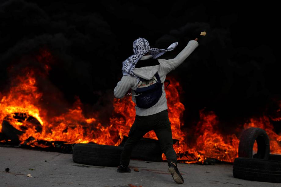 Manifestante palestino lança pedras contra as tropas israelenses durante confronto em um protesto contra a decisão do presidente dos Estados Unidos, Donald Trump, de reconhecer Jerusalém como a capital de Israel - 07/12/2017