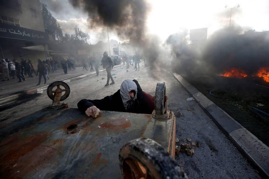 Manifestante palestino se protege atrás de uma caçamba durante confronto com as tropas israelenses em protesto contra a decisão do presidente dos Estados Unidos, Donald Trump, de reconhecer Jerusalém como a capital de Israel - 07/12/2017