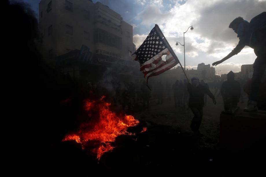 Manifestante palestino queima uma bandeira dos Estados Unidos durante confrontos com tropas israelenses perto do assentamento judeu de Beit El, perto da cidade de Ramallah, na Cisjordânia - 07/12/2017