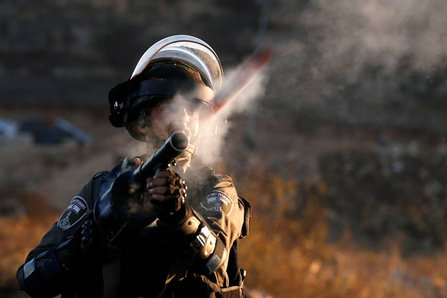 Um policial israelense de fronteira atira bombas de gás contra manifestantes palestinos, em Ramallah - 08/12/201