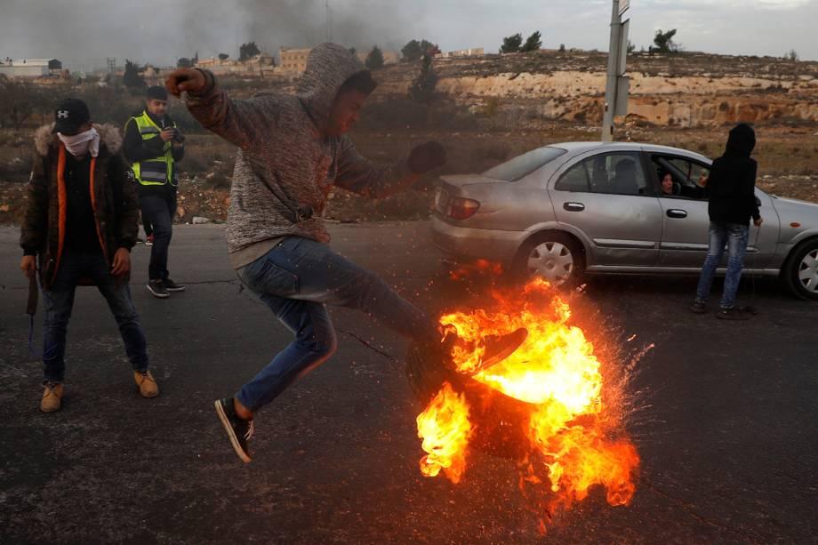 Palestino chuta pneu em chamas durante confronto com tropas israelenses, em protesto realizado contra a decisão do presidente dos Estados Unidos, Donald Trump, de reconhecer Jerusalém como a capital de Israel - 10/12/2017