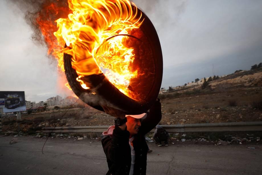 Palestino carrega pneu em chamas durante confronto com tropas israelenses, em protesto realizado contra a decisão do presidente dos Estados Unidos, Donald Trump, de reconhecer Jerusalém como a capital de Israel - 10/12/2017