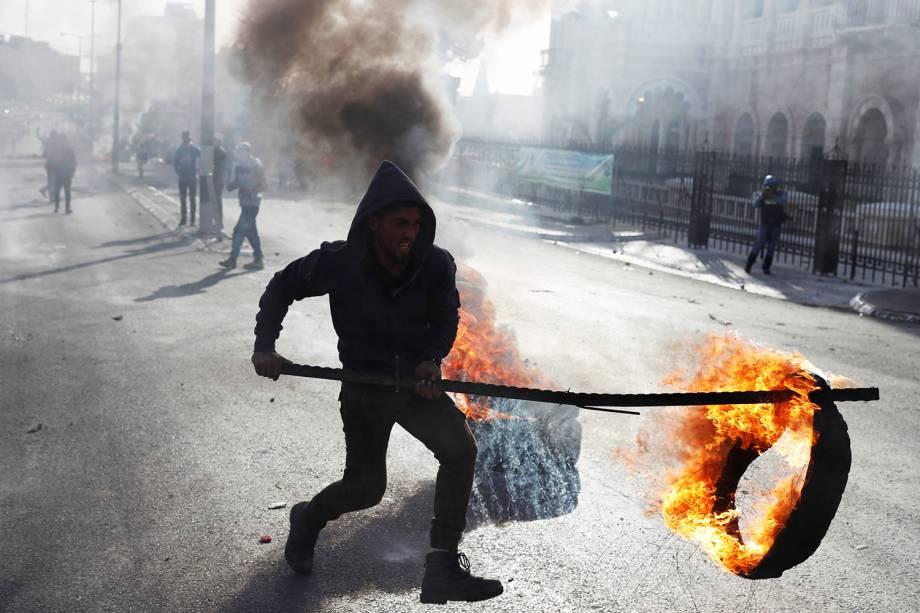 Manifestante palestino faz barricada com pneus na cidade de Belém, região da Cisjordânia, durante protestos contra a decisão do presidente dos Estados Unidos, Donald Trump, de reconhecer Jerusalém como a capital de Israel - 10/12/2017