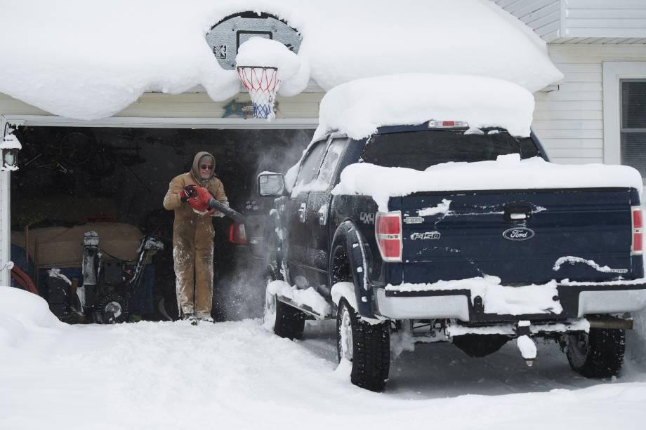 Um homem utiliza o soprador para retirar a neve de cima da sua caminhonete, em Erie, na Pensilvânia - 27/12/2017