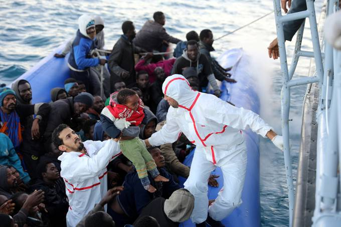 Migrant child is carried as other migrants in a dingy are rescued by Libyan coast guards off the coast of Garabulli
