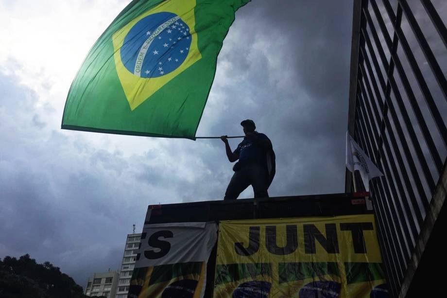 Homem balança uma bandeira do Brasil durante ato a favor  da condenação do ex-presidente Lula em frente ao MASP, na Avenida Paulista, em São Paulo - 24/01/2018